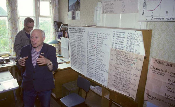 The great Russian mineralogist A.P. Khomyakov in his laboratory in Khibiny in 1992, with list of possible new minerals behind him (photo © O.T. Ljostad/mindat.org)