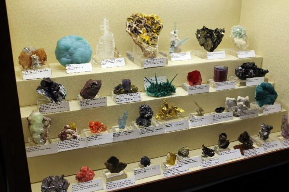 Mixed case of mineral specimens displayed on traditional fabric covered risers.