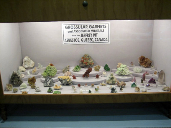 Display case showing mixed size mineral specimens from a single locality.