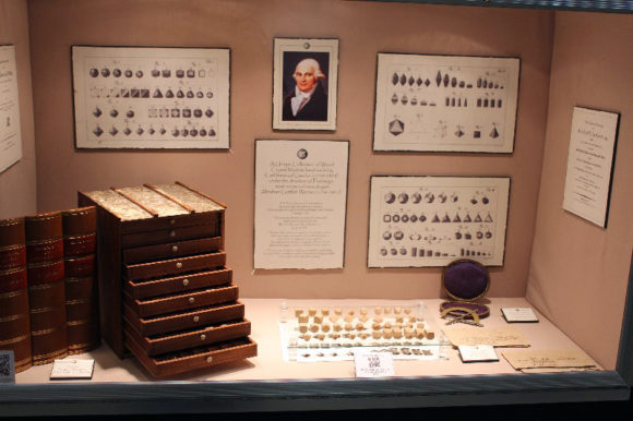 Educational display showing historical crystal models and drawings.